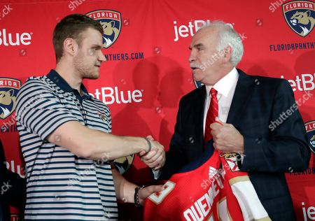 Florida Panthers hockey captain Aleksander Barkov, of Finland, left, shakes hands with Joel Quenneville, who was introduced as the Florida Panthers new head coach at news conference, in Sunrise, Fla