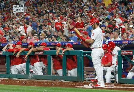A fan, left, holds up a sign as Philadelphia Phillies' Bryce Harper, right, gets ready for his at-bat during the seventh inning of a baseball game against the Washington Nationals, in Philadelphia