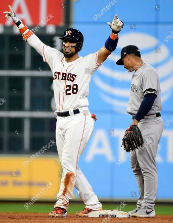 Houston Astros' Robinson Chirinos, left, reacts after his game-tying two-run double as New York Yankees shortstop Gleyber Torres looks on during the seventh inning of a baseball game, in Houston