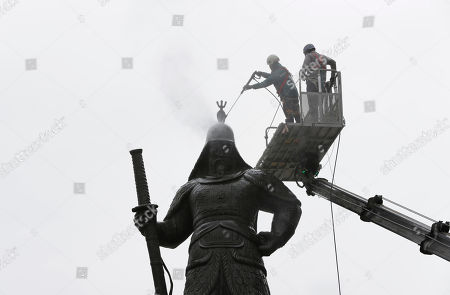 A worker cleans the statue for a spring cleaning in downtown Seoul, South Korea, . The statue is, Adm. Yi Sun-shin, the national hero who won a major naval victory over Japan in the 16th century