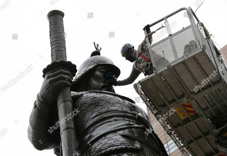 A worker cleans a statue for a spring cleaning in downtown Seoul, South Korea, . The statue is, Adm. Yi Sun-shin, the national hero who won a major naval victory over Japan in the 16th century