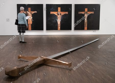Stock Picture of A woman stands between artworks (back, L-R) 'Gestas', 'Jesus' and 'Dismas' by George Condo and (front) 'Mandi XV' by Kris Martin during a press preview of the exhibition 'BEYOND' at the me Collectors Room Berlin / Olbricht Collection, in Berlin, Germany, 09 April 2019. The exhibition will feature works by seven international artists from 10 April to 18 August.