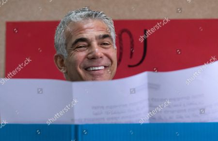 Yair Lapid, the number two on the centrist Blue and White Israeli party, looks up while selecting his ballot as he votes in the Israeli general elections, in a school in the Ramat Aviv area of Tel Aviv, Israel, 09 April 2019. Polls opened nation-wide as Israel's 2019 Knesset election is underway, with some 6.3 million eligible voters.