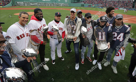 Stock Image of Matthew Slater, Mike Lowell, Steve Pearce, Rob Gronkowski, Patrick Chung, Julian Edelman, Stephon Gilmore, Duron Harmon, Deatrich Wise. New England Patriots and Boston Red Sox players hold Super Bowl and World Series trophies before the home opener baseball game between the Red Sox and the Toronto Blue Jays, in Boston. From left they are, Patriots' Matthew Slater, Red Sox's Mike Lowell and Steve Pearce, Patriots' Rob Gronkowski, Patrick Chung, Julian Edelman, and Stephon Gilmore (24). At rear are Duron Harmon, behind Gronkowski, and New England Patriots' Deatrich Wise, behind Edelman