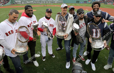 Mike Lowell, David Ortiz, Steve Pearce, Rob Gronkowski, Patrick Chung, Julian Edelman, Duron Harmon, Deatrich Wise. New England Patriots and Boston Red Sox players hold Super Bowl and World Series trophies before the home opener baseball game between the Red Sox and the Toronto Blue Jays, in Boston. From left they are, Red Sox's Mike Lowell, David Ortiz and Steve Pearce, Patriots' Rob Gronkowski, Patrick Chung and Julian Edelman. At rear are Duron Harmon, behind Gronkowski, and Deatrich Wise, behind Edelman
