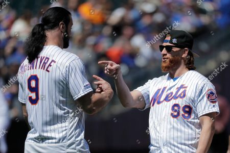 Wrestlers Drew McIntyre, left, and Curt Hawkins talk near the mound before Hawkins threw a ceremonial first pitch prior to a baseball game between the New York Mets and the Washington Nationals, in New York