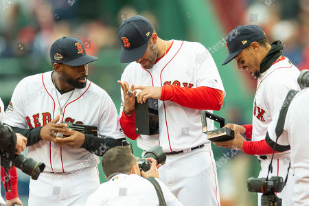 Boston Red Sox center fielder Jackie Bradley Jr. (L) Boston Red Sox left fielder J.D. Martinez (C) and Boston Red Sox right fielder Mookie Betts (R) look over their World Series Championship rings during pre-game ceremonies before the start of the Boston Red Sox home opener against the Toronto Blue Jays at Fenway Park in Boston, Massachusetts, USA 09 April 2019.