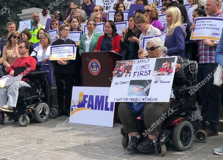 Stock Photo of Colorado Democratic Sens. Angela Williams and Faith Winter listen behind the podium as activist Judith Marquez speaks in favor of their paid family leave bill at a rally outside the statehouse, in Denver