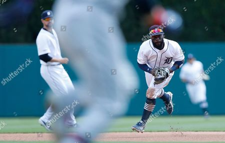 Detroit Tigers second baseman Josh Harrison, right, fields the ball hit by Cleveland Indians' Carlos Santana during the fourth inning of a baseball game, in Detroit