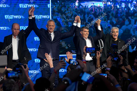 Blue and White party leaders from left Moshe Yaalon, Benny Gantz, Gabi Ashkenazi and Yair Lapid raise hands in front of their supporters after Israeli general elections polls closed, in Tel Aviv
