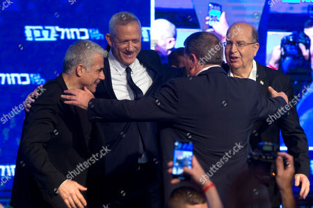 Blue and White party leaders from left Yair Lapid, Benny Ganzt, Gabi Ashkenaz Yair Lapid and Moshe Yaalon, hug in front of their supporters after Israeli general elections polls closed, in Tel Aviv