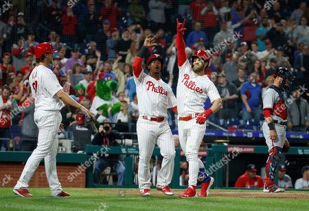 Philadelphia Phillies' Bryce Harper, center right, celebrates his three-run home run with Jean Segura, center left, and Aaron Nola, left, as Washington Nationals catcher Yan Gomes, right, waits during the third inning of a baseball game, in Philadelphia