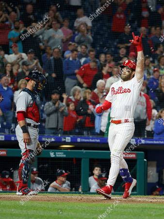 Philadelphia Phillies' Bryce Harper, right, gestures as he scores on his three-run home run, next to Washington Nationals catcher Yan Gomes during the third inning of a baseball game, in Philadelphia
