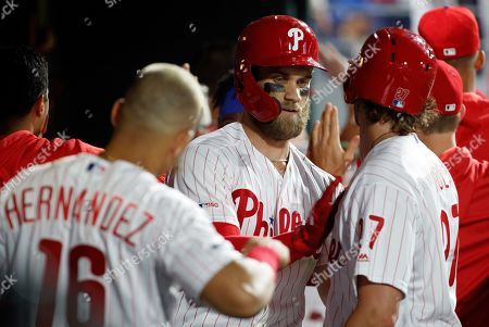 Philadelphia Phillies' Bryce Harper, center, celebrates his three-run home run with Aaron Nola, right, and Cesar Hernandez, left, during the third inning of the team's baseball game against the Washington Nationals, in Philadelphia