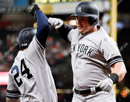 New York Yankees' Luke Voit, right, celebrates his solo home run off Houston Astros starting pitcher Gerrit Cole with Gary Sanchez during the first inning of a baseball game, in Houston