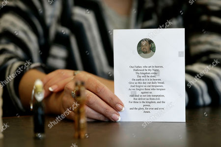 In Raleigh, N.C. Heather Allen holds a photo of her father, Lee Wayne Hunt, from his memorial. Even though Lee Wayne Hunt died as a prisoner found guilty of a double murder, his family says he never gave up hope of proving his innocence