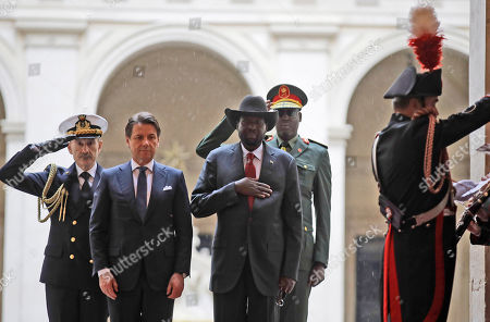 South Sudan President Salva Kiir Mayardit, center, and Italian Premier Giuseppe Conte, second from left, listen to the national anthems upon Mayardit's arrival at Chigi palace, Government's office, . The Vatican has invited South Sudan's president and opposition leader Riek Machar for a two-day spiritual retreat, attended also by Mayardit, meant to foster peace after the country's five-year civil war and build confidence in its fragile peace deal