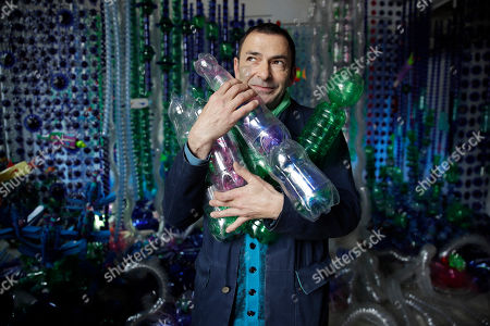 "Spanish designer Arsenio Rodriguez holds plastic bottles in front of his installation made with 20.000 recycled plastic bottles, displayed during the 'RO Plastic exhibition', part of the Salone del Mobile Furniture Fair week, in Milan, Italy, Wednesdays, . The Rossana Orlandi gallery has organized a ""Plastic Prize"", on the sidelines of the Milan Furniture fair week, challenging designers to create projects aimed at overcoming the global problem of plastic pollution"