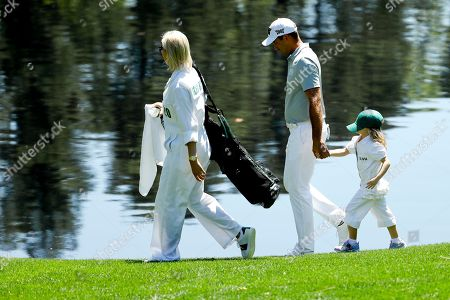 Charl Schwartzel, of South Africa, with his wife Rosalind and daughter Olivia walk to the fourth hole during the par-3 golf tournament at the Masters, in Augusta, Ga