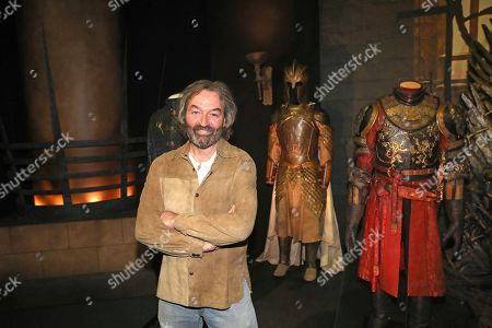 Actor Ian Beattie who starred in the Game of Thrones stands beside his costume during the launch of The Game of Thrones Touring Exhibition at the Titanic Exhibition centre in Belfast, Northern Ireland, . The exhibition is made up of authentic costumes, props and settings from seven seasons