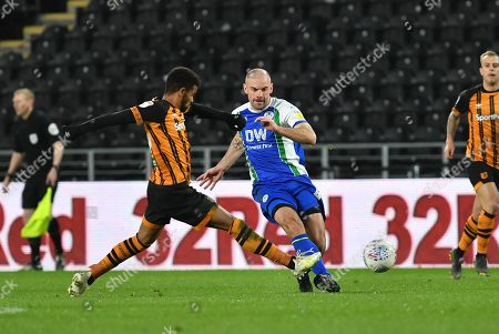 Hull City forward Fraizer Campbell (25) and Wigan Athletic midfielder Darron Gibson (4)  during the EFL Sky Bet Championship match between Hull City and Wigan Athletic at the KCOM Stadium, Kingston upon Hull