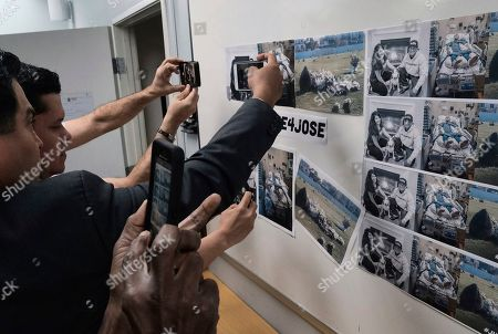 Journalists take photos posted of Jose Luis Ibarra Bucio, in a coma and restrained in a hospital bed prior to a news conference at the offices of the Coalition for Humane Immigrant Rights of Los Angeles (CHIRLA), in Los Angeles. The family of the 27-year-old Bucio who died after a short stint in a California immigration detention facility demanded answers Wednesday about what happened to him and the timing of his release. Melissa Castro said her husband, was released as his health deteriorated from a brain hemorrhage and while he was in a coma from which he never awoke
