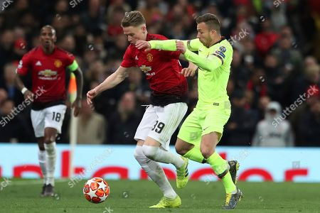 Manchester United's Scott McTominay, left, and Barcelona's Arthur fight for the ball during the Champions League quarterfinal, first leg, soccer match between Manchester United and FC Barcelona at Old Trafford stadium in Manchester, England