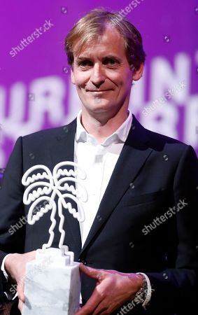 Lars Kraume poses with the Best Music award for the TV series 'Nehama' at the Cannes Series Festival in Cannes, France, 10 April 2019.