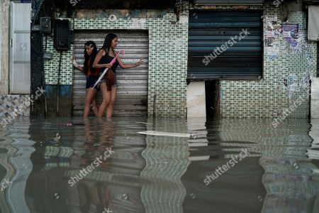 Women wade through a flooded street in Rio de Janeiro, Brazil, . Heavy rains killed at least 10 people and left a trail of destruction in Rio de Janeiro on Tuesday, raising questions about the city's preparedness to deal with recurring extreme weather