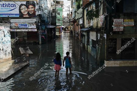 Children walk through a flooded street in Rio de Janeiro, Brazil, . Heavy rains killed at least 10 people and left a trail of destruction in Rio de Janeiro on Tuesday, raising questions about the city's preparedness to deal with recurring extreme weather