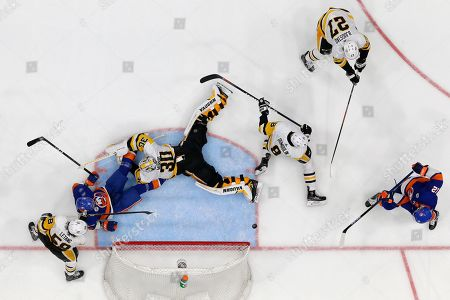 Stock Image of New York Islanders right wing Josh Bailey, bottom right, scores during overtime of Game 1 of an NHL hockey first-round playoff series against the Pittsburgh Penguins, in Uniondale, N.Y. Around the goal are Islanders' Mathew Barzal, second from left, and Penguins' Kris Letang (58), goaltender Matt Murray (30), Brian Dumoulin (8) and Nick Bjugstad (27). The Islanders won 4-3