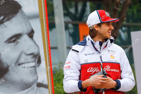 Italian Formula One driver Antonio Giovinazzi (R) of Alfa Romeo Racing walks past a large portrait of Former Brazilian Formula One driver Emerson Fittipaldi to commemorate F1 1000th race on the paddock ahead of the Chinese Formula One Grand Prix at the Shanghai International circuit in Shanghai, China, 11 April 2019. The 2019 Chinese Formula One Grand Prix will take place on 14 April.