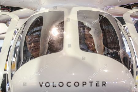 Stock Picture of Two men sit in the cockpit of a Volocopter 2X, an electric helicopter with 18 rotor blades made by Volocopter, at the Rotorcraft Asia trade show at the Changi Exhibition Centre in Singapore, 11 April 2019. The Civil Aviation Authority of Singapore announced that trials for air taxis would begin in the Southern region of Singapore later this year. The Volocopter 2X is battery powered and can fly at a top speed of 100 kilometers per hour and has a maximum takeoff weight of 450 kg.