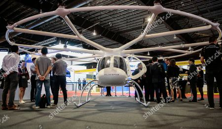 Visitors stand around a Volocopter 2X, an electric helicopter with 18 rotor blades made by Volocopter, at the Rotorcraft Asia trade show at the Changi Exhibition Centre in Singapore, 11 April 2019. The Civil Aviation Authority of Singapore announced that trials for air taxis would begin in the Southern region of Singapore later this year. The Volocopter 2X is battery powered and can fly at a top speed of 100 kilometers per hour and has a maximum takeoff weight of 450 kg.