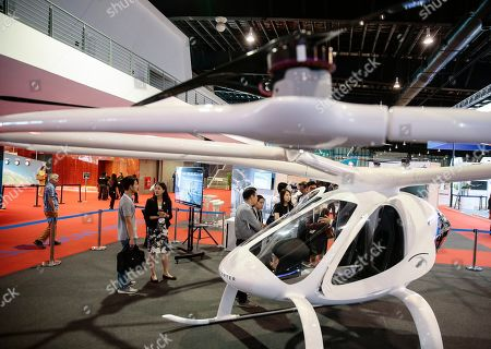 The Volocopter 2X, an electric helicopter with 18 rotor blades made by Volocopter, is displayed at the Rotorcraft Asia trade show at the Changi Exhibition Centre in Singapore, 11 April 2019. The Civil Aviation Authority of Singapore announced that trials for air taxis would begin in the Southern region of Singapore later this year. The Volocopter 2X is battery powered and can fly at a top speed of 100 kilometers per hour and has a maximum takeoff weight of 450 kg.
