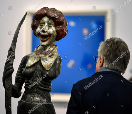 A visitor watches a sculpture by artists Jake and Dinos Chapman at the ART COLOGNE fair in Cologne, Germany, . The yearly art fair for international galleries present art of the 20th and 21st centuries since 1967 in Cologne