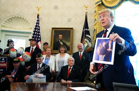 Donald Trump, Allen Jones, Paul Kriner, Sidney Walton, Floyd Wigfield. President Donald Trump is presented with a picture by a World War II veteran in the Oval Office of the White House in Washington