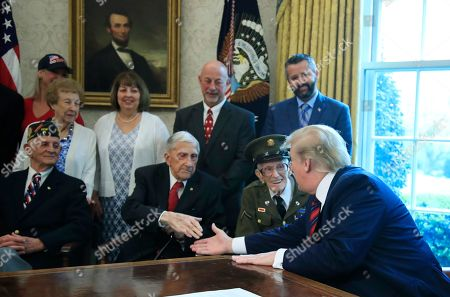 Donald Trump, Allen Jones, Paul Kriner, Floyd Wigfield, Sidney Walton. President Donald Trump is joined by World War II veterans, seated from left, Allen Jones, Paul Kriner and Floyd Wigfield, in the Oval Office of the White House in Washington