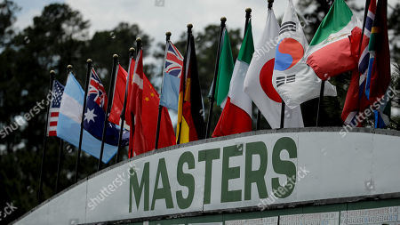 Flags blow in the wind at the large scoreboard at the Masters golf tournament, in Augusta, Ga