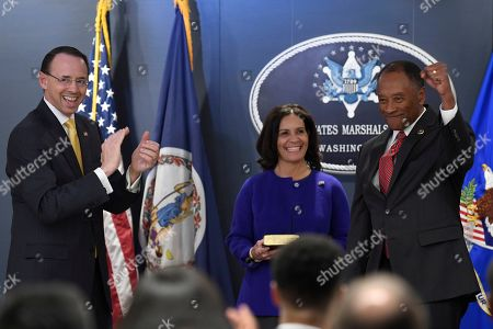 Stock Picture of Rod Rosenstein, Donald Washington, Yvonne Washington. Deputy Attorney General Rod J. Rosenstein, left, applauds after swearing in the new U.S. Marshals Service Director Donald Washington during an Installation Ceremony in Arlington, Va., . Washington's wife Yvonne Washington, center, watches