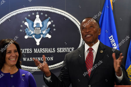 Stock Image of Donald Washington, Yvonne Washington. The newly sworn in U.S. Marshals Service Director Donald Washington, left, speaks during his Installation Ceremony in Arlington, Va., as his wife Yvonne Washington, left, listens