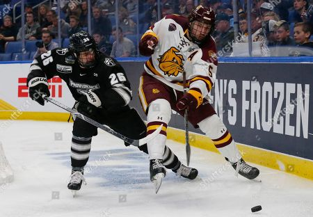 Stock Picture of Minnesota Duluth defenseman Nick Wolff (5) and Providence forward John McDermott (26) battle for the puck during the first period in the semifinal of the Frozen Four NCAA college hockey tournament, in Buffalo, N.Y