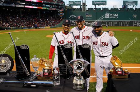 Boston Red Sox's Mookie Betts, left, J.D. Martinez, center, and Jackie Bradley Jr. stand with their various 2018 awards including Silver Sluggers, Gold Gloves and the AL MVP before a baseball game between the Red Sox and the Toronto Blue Jays, at Fenway Park in Boston