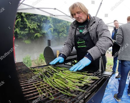 """Stock Image of Gary Larsen, of Pasco, Wash., the chair of the Washington Asparagus Commission, grills Washington-grown asparagus, to be served during the Washington Cattlemen's Association's annual """"Beef Day on the Hill,"""", at the Capitol in Olympia, Wash. Ranchers, farmers, and other volunteers served up free samples asparagus and beef to promote Washington ranching and agriculture in the final weeks of the regular session of the Legislature"""