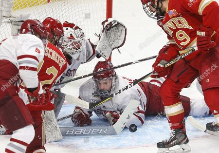 Massachusetts Minutemen defenseman Jake McLaughlin (27) blocks a to assist goaltender Filip Lindberg (35) during the first period of play in the NCAA Frozen Four Men's Hockey Semi-Final game between the Denver Pioneers and Massachusetts Minutemen at the KeyBank Center in Buffalo , N.Y. (Nicholas T