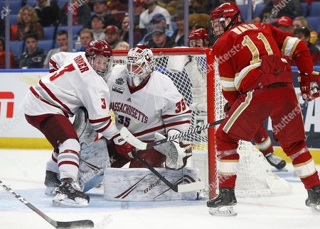 Massachusetts Minutemen defenseman Ty Farmer (3) assists goaltender Filip Lindberg (35) in front of the net with Denver Pioneers forward Tyler Ward (11) looking for a rebound during the second period of play in the NCAA Frozen Four Men's Hockey Semi-Final game between the Denver Pioneers and Massachusetts Minutemen at the KeyBank Center in Buffalo , N.Y. (Nicholas T