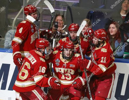 Denver Pioneers forward Cole Guttman (19) celebrates with teammates forward Jake Durflinger (16), forward Tyler Ward (11), defenseman Griffin Mendel (4), and defenseman Michael Davies (21) after scoring the Pioneers 2nd goal of the game during the third period of play in the NCAA Frozen Four Men's Hockey Semi-Final game between the Denver Pioneers and Massachusetts Minutemen at the KeyBank Center in Buffalo , N.Y. (Nicholas T