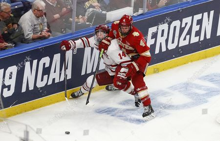 Stock Picture of Massachusetts Minutemen forward Jacob Pritchard (14) battles with Denver Pioneers defenseman Griffin Mendel (4) for the puck during overtime in the NCAA Frozen Four Men's Hockey Semi-Final game between the Denver Pioneers and Massachusetts Minutemen at the KeyBank Center in Buffalo , N.Y. Massachusetts defeated Denver 4-3 to advance to the National Championship game. (Nicholas T
