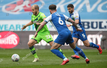 Teemu Pukki of Norwich City battles with Sam Morsy of Wigan Athletic and Danny Fox of Wigan Athletic