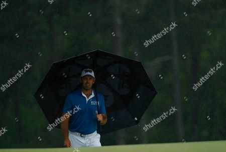 Charl Schwartzel, of South Africa, waits in the rain on the 18th hole during the second round for the Masters golf tournament, in Augusta, Ga
